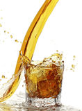 Yellow liquid splash. With glass and ice Royalty Free Stock Image