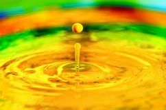 A yellow liquid water drop splashing in liquid paint Royalty Free Stock Photo