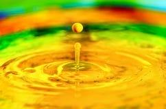 A yellow liquid water drop splashing in liquid paint. Yellow liquid paint drop splashing into paint Royalty Free Stock Photo