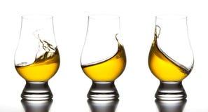 Yellow liquor in whiskey glass splash Stock Images