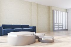 Yellow living room, blue sofa and posters side. Yellow living room interior with a wooden floor, a large poster, and a soft blue sofa next to a round table. A Stock Images
