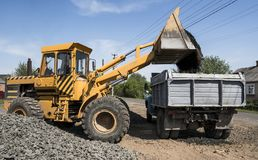 Yellow loader delivering stone gravel into truck during road construction works. The stones for the road. Unloading royalty free stock photos