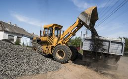 Yellow loader delivering stone gravel into truck during road construction works. The stones for the road. Unloading stock image