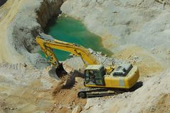 Yellow loader, dredge. Big yellow loader carries a large stone in the quarry Stock Images