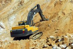 Yellow loader, dredge. Big yellow loader carries a large stone in the quarry Stock Image