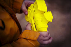 Yellow locomotive sand form in boys hands Stock Photography