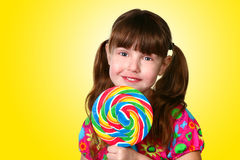 Yellow Lollipop Girl. Adorable Young Child Holding Large Lollipop on Yellow Background royalty free stock photo