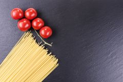 Yellow raw spaghetti and cherry tomatoes on black slate plate Stock Images