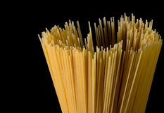 Yellow long spaghetti on black background. Thin pasta arranged in rows. Yellow italian pasta. Long spaghetti. Raw spaghetti royalty free stock images