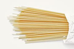 Yellow long spaghetti on a light background. Thin pasta arranged in rows. Italian raw pasta. Food background royalty free stock image