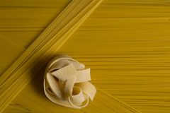 Yellow long spaghetti. Uncooked pasta texture background stock image