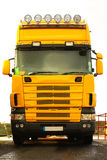 Yellow lorry. On the road closeup Stock Photo