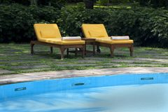 Yellow lounge chairs by a pool. Lounge chairs poolside at a hotel Stock Photos