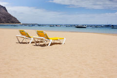 Yellow lounge chairs on the sea beach Stock Photo