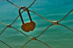 Yellow love lock on bridge railing. Close-up of a two heart-shaped yellow love lock hanging on a bridge railing in front of the aquamarine sea in sunlight royalty free stock photo