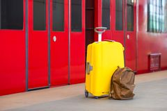 Yellow luggage with passports and brown backpack Stock Photos