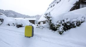 Yellow luggage on the road with snow as background stock photos