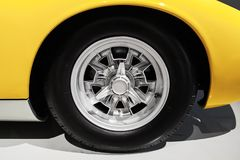 Yellow luxury Italian vintage sport car wheel. On chromed disc, close up photo with selective focus Stock Image