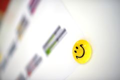 Yellow magnet with smiley face on flipchart Royalty Free Stock Photo
