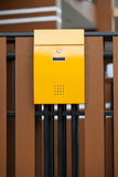 Yellow mailbox on brown wall Royalty Free Stock Photo