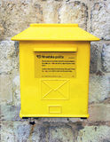 Yellow mailbox. CROATIA. DUBROVNIK - JUNE 20, 2017: A modern yellow mailbox hangs on an old city wall in a summer day Stock Image