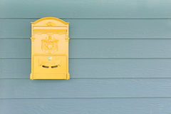 Yellow mailbox with green wood Stock Photos
