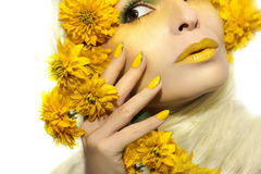Yellow makeup and manicure. Yellow makeup and manicure with a sharp oval shape of the nails on the girl with the flowers stock photography