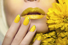 Yellow makeup and manicure. Yellow makeup and manicure with a sharp oval shape of the nails on the woman with the flowers closeup royalty free stock images