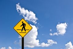 A yellow man walking sign with blue sky Stock Image