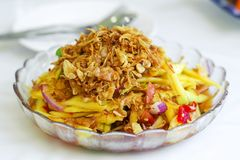 Yellow mango salad with oyster and shallot. Garnish with crispy shallot Stock Image