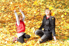Yellow maple leaves. Mom and daughter throw each other yellow maple leaves stock images