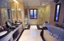 Yellow marble bathroom. Marble bathtub.dark table.modern design.big mirrior Royalty Free Stock Image