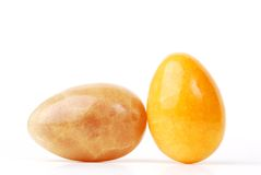 Yellow marble eggs. Two marble eggs, one yellow and one pueple, isolated on white Stock Image