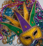 A yellow Mardi Gras mask and beads. A yellow Mardi Gras jester mask and beads