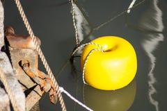 Yellow marker buoy. Floating yellow marker buoy with hole Royalty Free Stock Photo