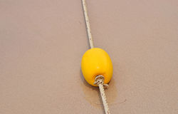 Yellow marker buoy on sand beach Stock Images