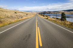 Yellow markings on a tarred highway. Leading straight off into the distance alongside a lake in low hills in a scenic landscape stock image