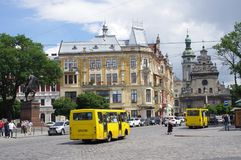 Yellow mini buses on the streets of Lviv in Ukraine. Yellow marshrutkas, a fixed-route minibus passing by Monument of King Danylo Halytskyi in the old town in Royalty Free Stock Images
