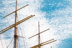 Yellow Masts. Two masts on a blue sky with white clouds background Royalty Free Stock Photography