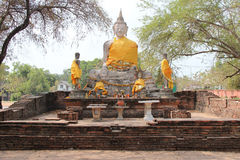 Yellow materials were draped around stone statues of Buddha in Ayutthaya (Thailand) Royalty Free Stock Photography