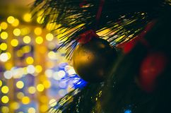 Yellow matte New Year decoration on the pine tree stock photos
