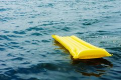 Yellow mattress in a blue sea floats, background stock photography