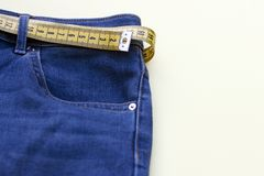 Yellow measure tape in jeans on background, concept of weight loss, copy space.  stock photo