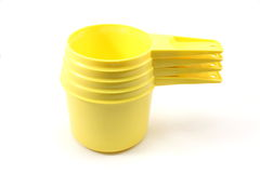 Yellow Measuring Cups. Stack of 4 yellow plastic measuring cups on a white background Stock Image