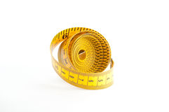 Yellow Measuring Tape. Roll of yellow measuring tape over white background Royalty Free Stock Photo