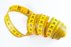 Yellow Measuring Tape. Roll of yellow measuring tape rolled up over white background Stock Photos