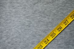 Yellow measuring tape lies on a gray knitted fabric. The measuring tape of yellow color with numerical indicators in the form of centimeters or inches lies on a stock photo
