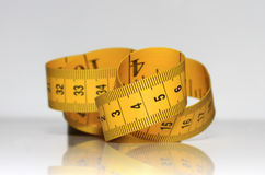 Yellow measuring tape is lying on a shiny Royalty Free Stock Image