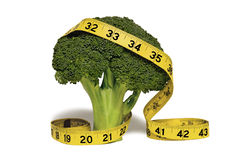 Measuring tape on broccoli. Yellow measuring tape wrapped around sprout of green broccoli isolated on white background Royalty Free Stock Image