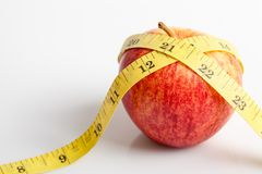 Yellow measuring tape with red apple Royalty Free Stock Photos